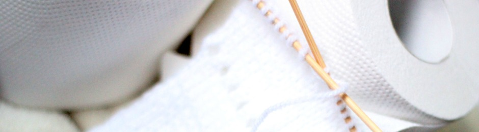 Ein weißes Strickstück mit einem löchrigen Rand, auf zwei Bambus-Sockennadeln, lehnt an an ein paar vollen Klopapierrollen.