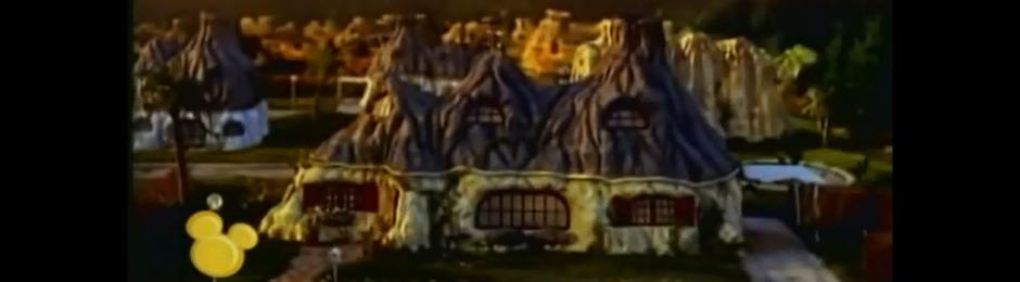 Flugsauerieransicht auf das Einfamilienhaus der Dinos. Es hat zwei Stockwerke, sieht aus wie drei Felsen nebeneinander, unten weiß angestrichen oben grau, in jedem Stockwerk jeweils drei Fenster. Morgend- oder abenddämmerung.