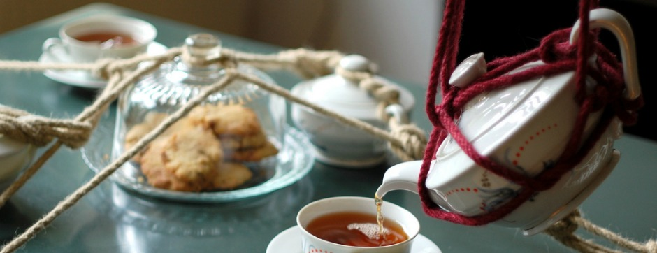 Ein mit Tassen und Keksen und Zuckerdose gedeckter Teetisch. In einer Tasse ist schon Tee, in die andere wird er gerade eingegossen. Der Clou: Das Service ist mit Bondageknoten gefesselt, die weiße Teekanne wird an einem roten Bondageseil gehalten, während der Tee eingeschenkt wird.