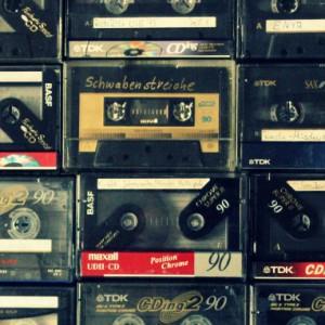Viele handbeschriftete Audiokassetten, die ordentlich nebeneinander liegen, in ihren Plastikhüllen.