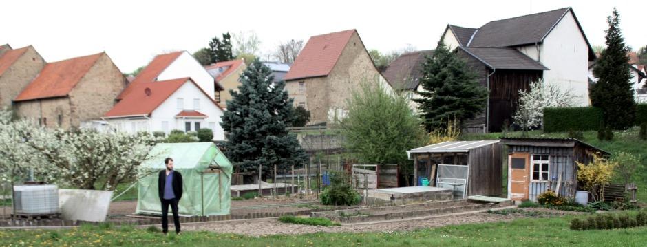 Dorf oder kleinstadtvorort Landschaft mit Einfamilienhäusern und ein paar Nadelbäumen im Hintergrund, davor ein Nutzarten mit Geächshaus und minikleiner Hütte. Der Autor Stefan Mesch steht vor dem Gewächshaus rum und guckt nach rechts.