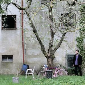 Eine verwaschengraue Hauswand, ein Baar Bäume, Gras. An einem Baum lehnt ein rosa Fahhrad, Efeu klebt am Haus. Was so rumsteht: ein weißer Gartenstuhl, eine Mülltonne, eine Wassertonne, ein großer Topf und der Autor Stefan Mesch.