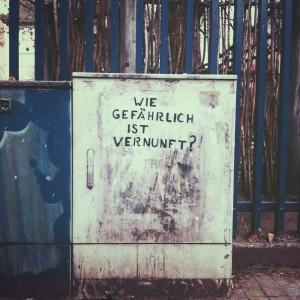 """Ein Stromkasten, auf dem mit Stencil """"Wie gefährlich ist Vernunft?"""" in Versalien gesprüht ist."""