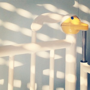 Die Ecke eines Krankenhausgitterbettchens im Licht halb heruntergelassener Jalousien. Der Pfosten des Bettes hat die form eines Entenkopfes.