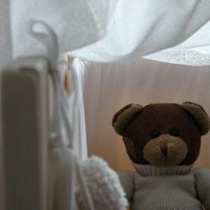 Himmel aus lichtdurchlässigem Stoff über einem Gitterbett aus Holz, und im Bett sitzt ein Teddy, der einen Pulli trägt.