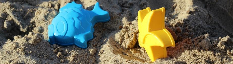 Zwei Sandförmchen im Sand; eins ein blauer Fisch, das andere ein gelber Stern