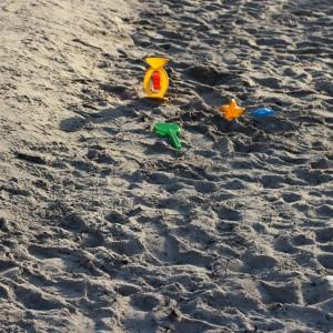 Ein Spielplatzsandkasten, weit wie ein Strand. Darin eine Sandmühle, eine Schaufel und zwei Förmchen. Und viel Sonne auf dem Sand.