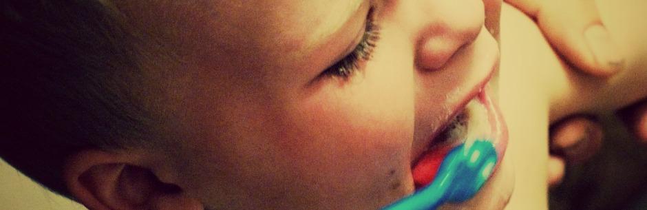 Ausschnitt eines Fotos von einem Kind, dem die Zähne geputzt werden und das dabei am Arm festgehalten wird und sich wehrt.